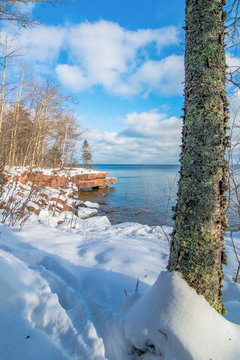 Beautiful trees and Lake Superior coastline in the cold and snow at Big Bay State Park - Madeline Island in Northern Wisconsin - sunny day with blue skies