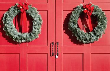 Christmas wreaths on red doors
