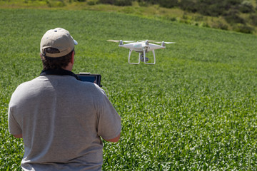 UAV Drone Pilot Flying and Gathering Data Over Country Farm Land