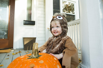 Smiling boy in Halloween costume sitting next to pumpkin