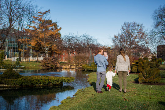 Behind view of a family walking together in a park in autumn sunshine