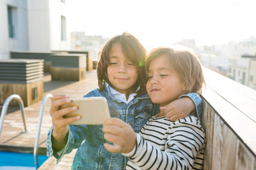 Two siblings making a self portrait with a smart phone on a rooftop