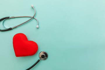 Simply minimal design with medicine equipment stethoscope or phonendoscope and red heart isolated on trendy pastel blue background. Instrument device for doctor. Health care life insurance concept
