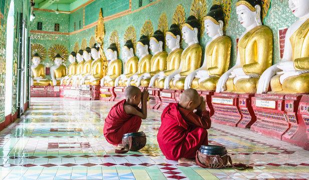 Asian Buddhist monks praying in temple, Mingun, Saigang, Myanmar
