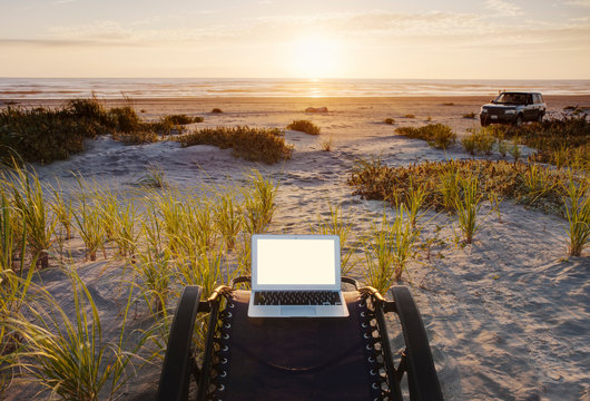 Laptop on deck chair overlooking sunset on beach