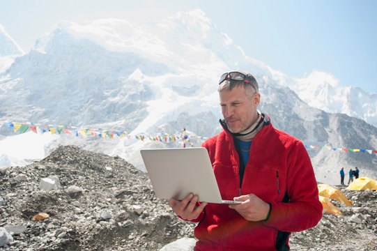 Man using laptop on snowy mountain