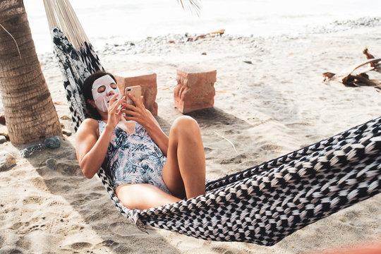 Woman wearing a beauty mask on a beach