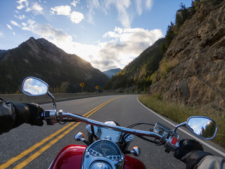 Riding on a motorcycle on a beautiful scenic road surrounded by the Canadian Mountains. Taken...