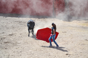 Girl bullfighting a bull with a red cape, in a ground bullring