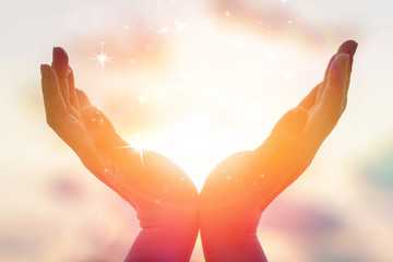 Silhouette of female hands holding sunset or sunrise for people energy and serene hope concept