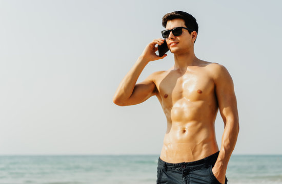 Portrait of young caucasian man in glasses with sexy body sunbathing  and Healthy Skin Sun Tan Tanning talking on mobile phone on the sea beach, guy over sea blue sky, communication concept.