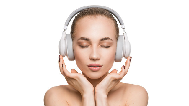 Woman in white headphones on white background listens to music with closed eyes.