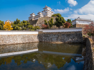 Himeji Castle and fortifications reflected in moats water on a beautiful day in autumn in Japan.