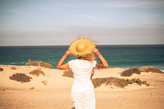 Summer holiday tourist vacation concept with people woman with white dress and hat viewed from back looking wonderful natural outdoor beach and feeling the breeze and the freedom