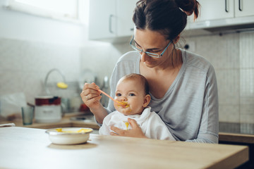 Young mother feeds the baby in the kitchen