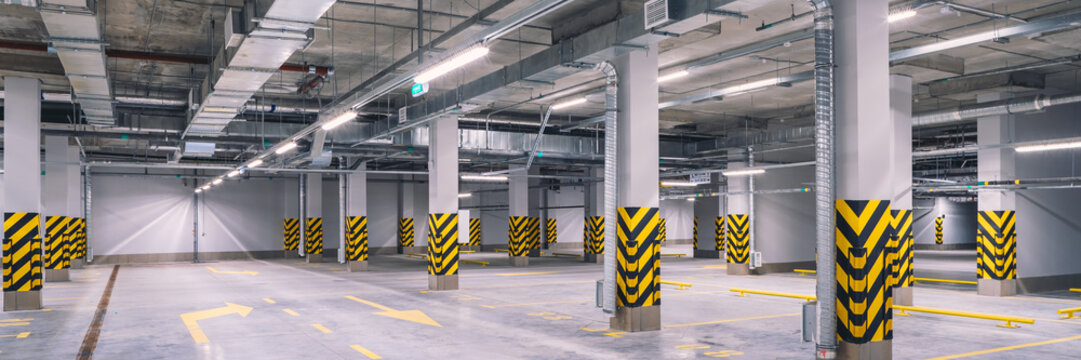 Empty shopping mall underground parking lot or garage interior with concrete stripe painted columns