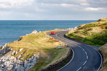 The eastern coast of Northern Ireland and Antrim Coastal Road, a.k.a. Causeway Coastal Route with a red car. Sunset light