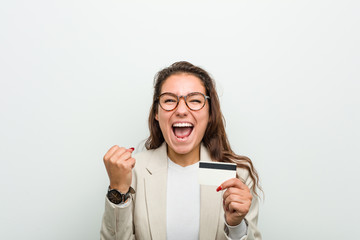 Young european business woman holding a credit card celebrating a victory or success