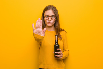 Young pretty caucasian woman putting hand in front. She is holding a beer.