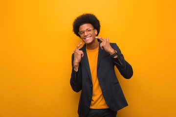 Young business african american man over an orange wall smiles, pointing mouth Wall mural