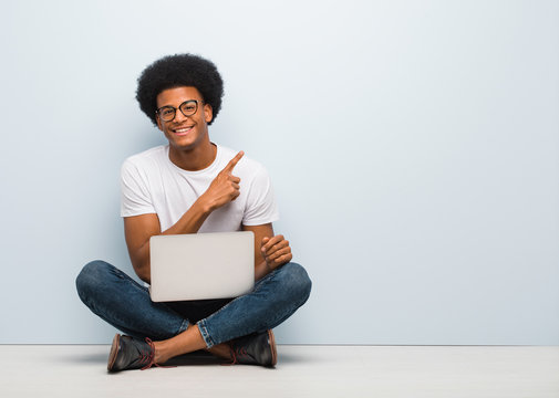 Young black man sitting on the floor with a laptop smiling and pointing to the side