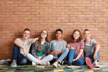 Group of teenagers sitting on floor near brick wall