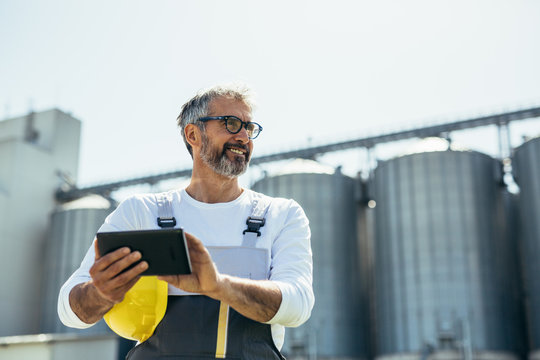 worker using tablet in front of grain silo