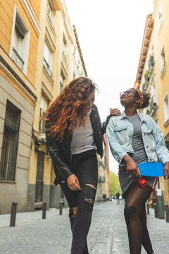 Two Teenage Latin Girls Walking Together in the Street.