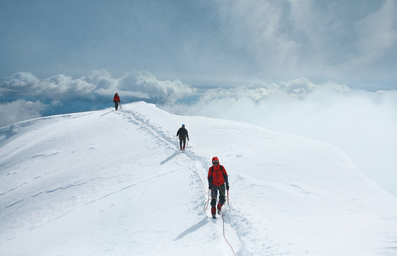 A group of mountaineers climbs to the top of a snow-capped mountain. Climbers are hiking on mountain peaks ridge. , Beautiful mountaineering tourism trekking. Concept of Motivation, Teamwork