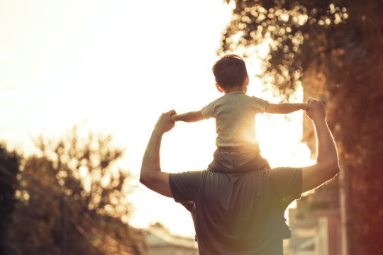 Happy family: Young father with his little child sitting on father's shoulders in Summer in City at Beautiful Sunset
