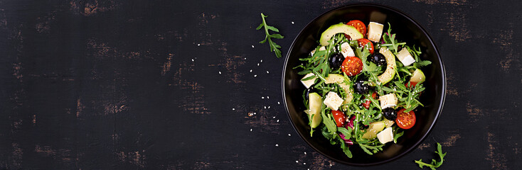 Green salad with sliced avocado, cherry tomatoes, black olives and cheese. Healthy diet vegetarian summer vegetable salad. Table setting. Food concept. Banner. Top view.