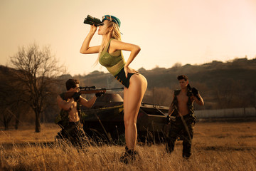 Sexy military girl with binoculars searching something ,on the highlands background with strong armed soldiers .Horizontal view.