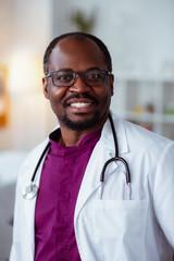 Handsome dark-skinned doctor smiling after good day at work