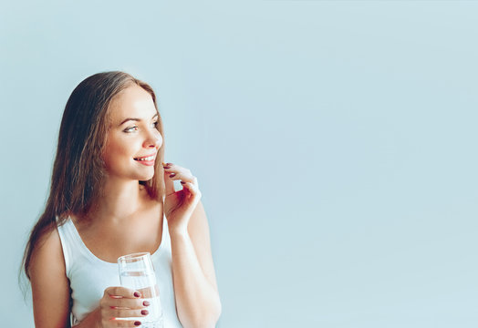 Beautiful Smiling Woman Taking Vitamin Pill With Cod Liver Oil Omega-3 And Holding  Glass Of Fresh Water In Morning.Vitamin D, E, A Fish. Dietary Supplement. Healthy Eating, Lifestyle.