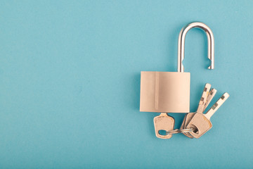 unlocked Padlock and bunch of key on the blue background.copy space for text