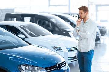 Final decision. Shot of a handsome young man standing in front of a new car at the dealership thinking rubbing his chin
