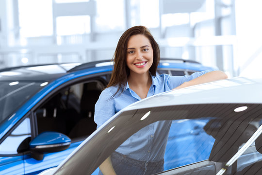 Perfect car for me. Gorgeous young woman smiling happily leaning on a car at the local car dealership