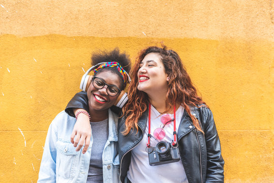 Two Teenage Latin Girls Standing Together Over a Yellow Wall.