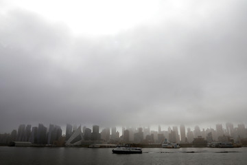 A New York Waterway ferry boat crosses the Hudson River as heavy fog hangs over the Manhattan skyline in New York
