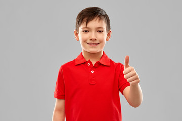 childhood, gesture and people concept - portrait of smiling little boy in red polo t-shirt showing thumbs up over grey background