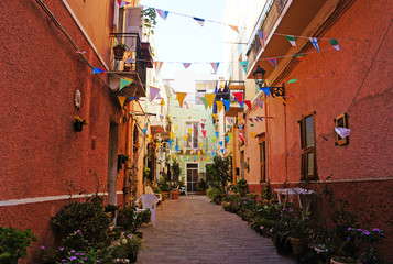 Holiday in the Italian city of streets with flags and ancient buildings.