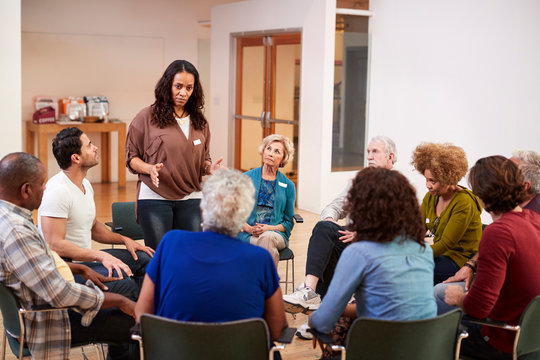 Woman Standing To Address Self Help Therapy Group Meeting In Community Center