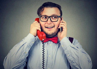 Happy businessman using cellphone and retro style telephone at once