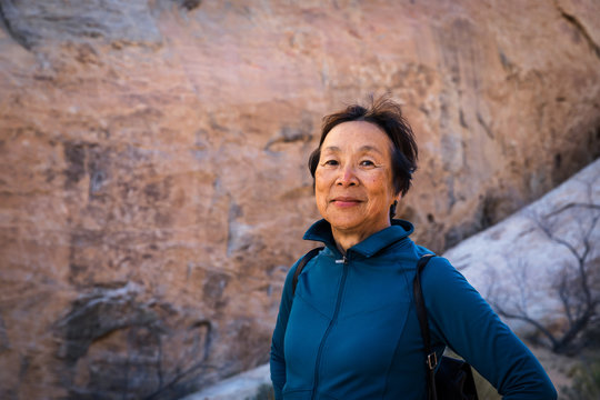 Portrait of  Senior Asian Woman in the desert landscape of Valley of Fire, Nevada, North America
