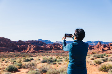 Senior Asian woman taking a photo of a desert landscape with her camera phone in Valley of FIre, Nevada, North America