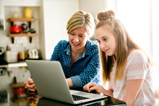 A mother using a laptop in kitchen with teenager