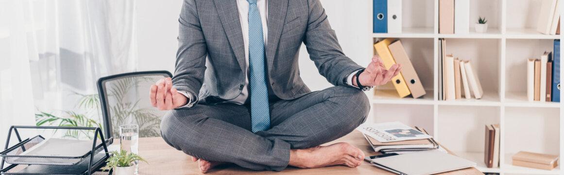 panoramic shot of businessman meditating in Lotus Pose on office desk