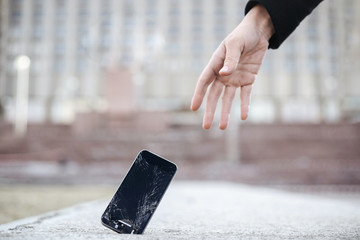 Close up of young woman pick up her broken smartphone with cracked screen glass
