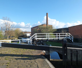 the historic castleton mill near armley in leeds and oddy lock gates and footbridge crossing the canal