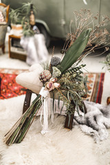 Stylish rustic boho wedding bouquet lying on the sand on the background of rustic decorations. Desert wedding, canyon